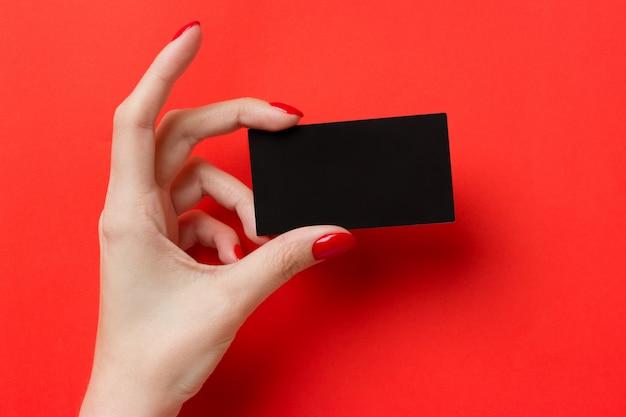 Le mani femminili con il manicure rosso tiene un biglietto da visita in bianco nero