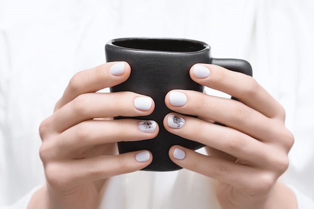 Le mani femminili con l'unghia bianca progettano la tenuta della tazza nera.