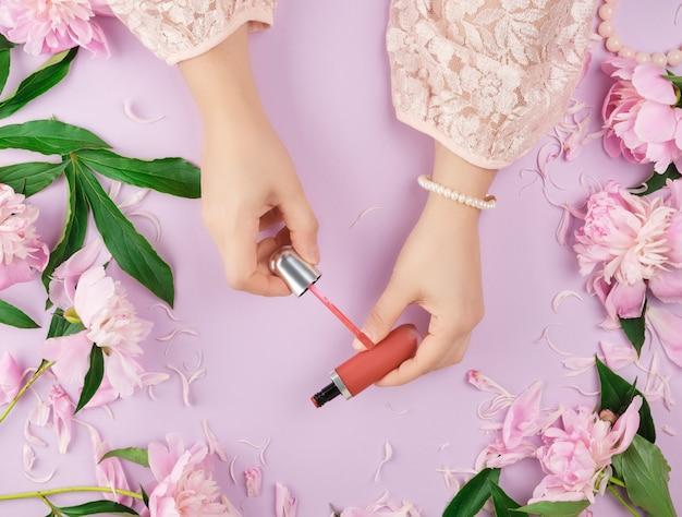 Le mani femminili con pelle chiara e liscia mantengono il rossetto rosso liquido in un tubo