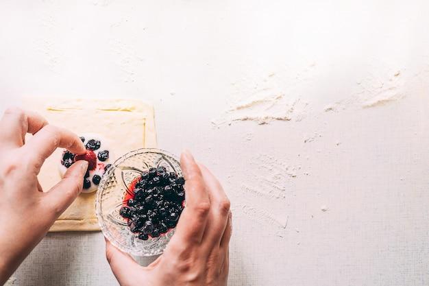 Le mani femminili cucinano la torta della pasta fatta in casa