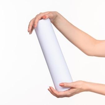 Le mani femminili del cilindro su priorità bassa bianca