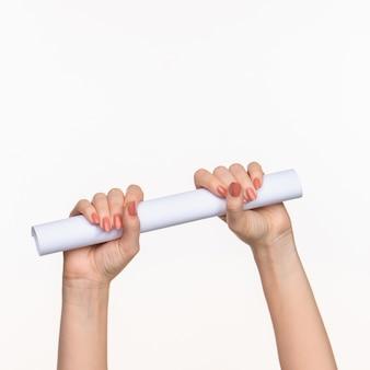 Le mani femminili del cilindro su spazio bianco