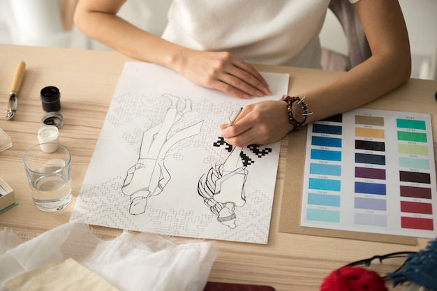 Le mani femminili del progettista che dipingono il ricamo modellano lo schema sullo schizzo di modo