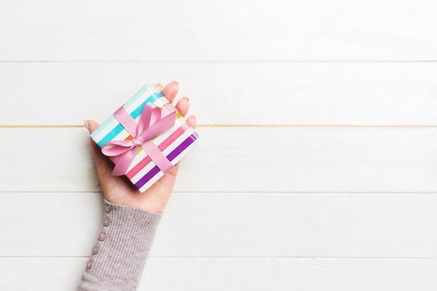 Le mani femminili di vista superiore che tengono il pacchetto fatto a mano nella scatola del presente di festa di natale o dell'altra festa, piano mettono sul copyspace bianco della tavola
