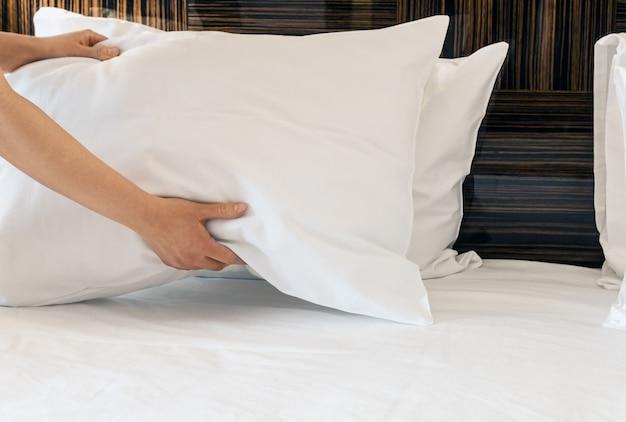 Le mani femminili hanno corretto il cuscino sul letto