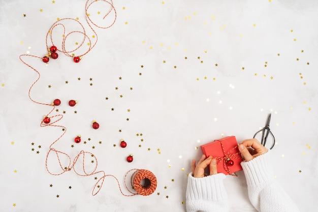 Le mani femminili in un maglione lavorato a maglia bianco imballano un contenitore di regalo