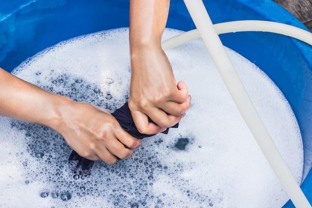 Le mani femminili lavano i vestiti a mano con il detersivo nel lavandino. messa a fuoco selettiva e spazio per il testo.