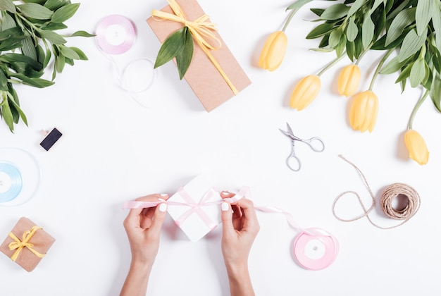 Le mani femminili legano una scatola rosa del nastro con i regali su una tavola bianca
