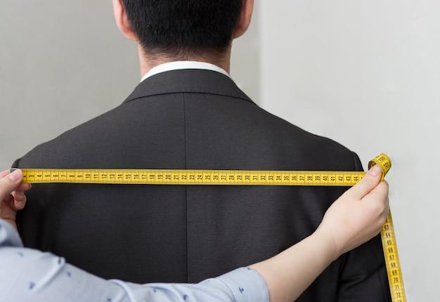 Le mani femminili misurano la giacca con un nastro che colpisce, vista posteriore, primo piano