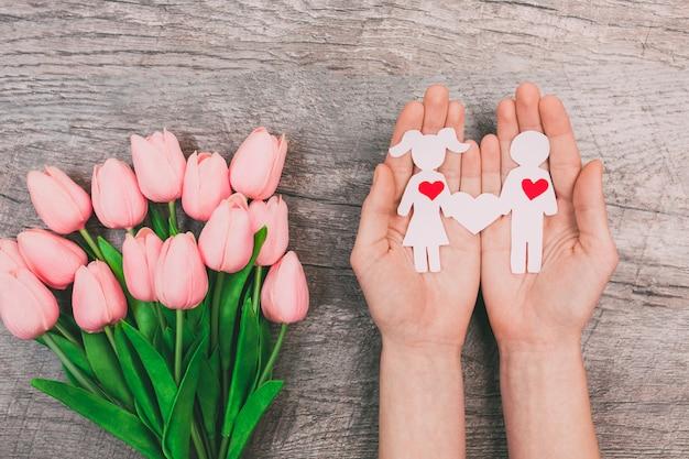 Le mani femminili mostrano due persone di carta, un uomo e una donna, su uno sfondo di legno. san valentino