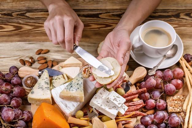 Le mani femminili spalmano il formaggio sul pane tostato.