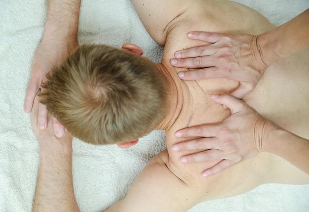 Le mani femminili stanno massaggiando la schiena di un uomo.