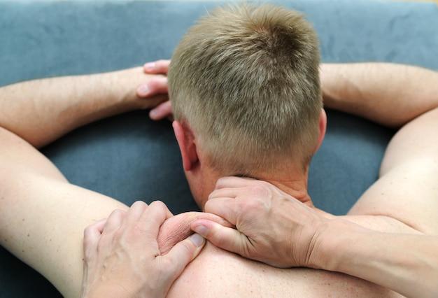 Le mani femminili stanno massaggiando la spalla di un uomo.