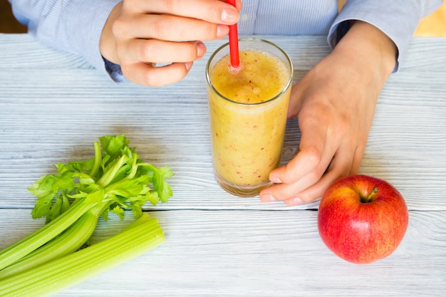 Le mani femminili tengono frullati di mele e sedano in un bicchiere con una cannuccia su un tavolo