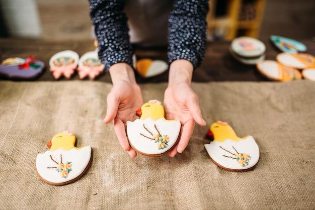 Le mani femminili tengono i biscotti dolci con le immagini