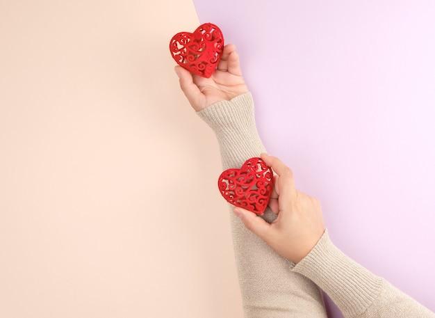 Le mani femminili tengono i cuori rossi