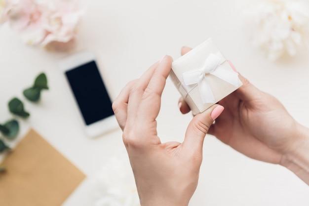 Le mani femminili tengono il contenitore di regalo bianco sopra dei fiori e del telefono. vista dall'alto
