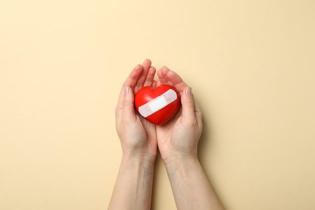 Le mani femminili tengono il cuore con cerotto adesivo su spazio beige, vista superiore