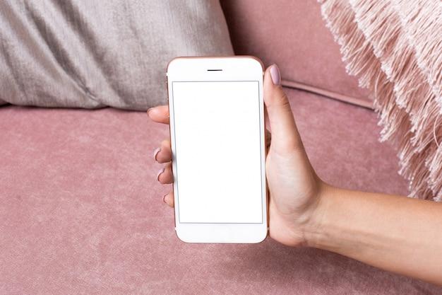 Le mani femminili tengono il telefono cellulare con lo schermo bianco deridono su su una superficie interna rosa