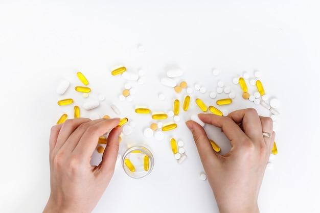 Le mani femminili tengono le pillole colorate multi su una superficie bianca. vista dall'alto. concetto di salute.