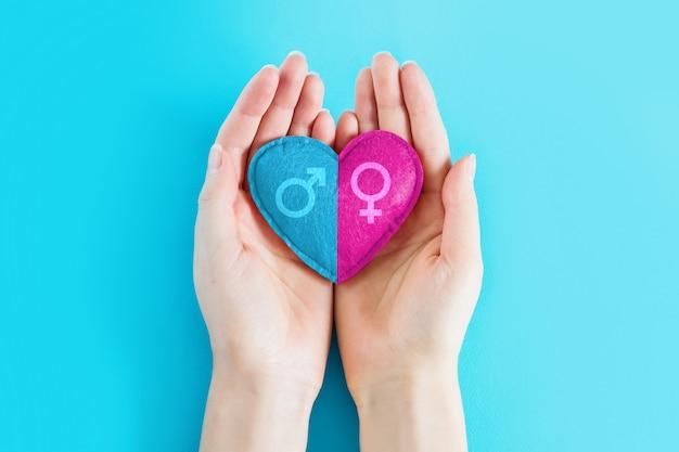 Le mani femminili tengono un cuore con un simbolo maschio e femminile su uno sfondo blu, copia spazio. ragazza o ragazzo, concetto di gravidanza. concetto di gemelli in gravidanza
