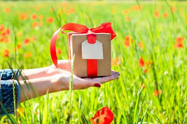 Le mani femminili tengono un regalo in una scatola artigianale, con un nastro e un'etichetta