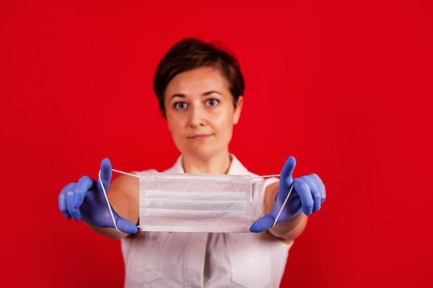 Le mani femminili tengono una mascherina medica. la giovane donna professionale del medico tiene una mascherina medica in sue mani. gruppo di protezione antivirus.