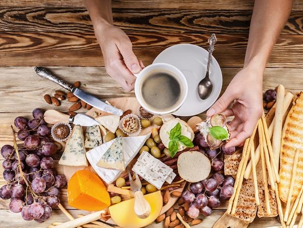 Le mani femminili tengono una tazza di caffè e brindano con formaggio