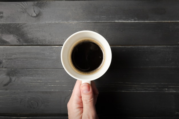 Le mani femminili tengono una tazza di caffè sul tavolo di legno