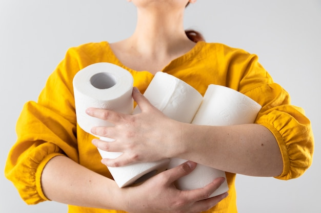Le mani femminili tiene molti rotoli di carta igienica su una parete grigia