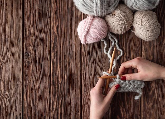 Le mani femminili tricottano su una tavola di legno con le palle del filo. concetto fatto a mano.