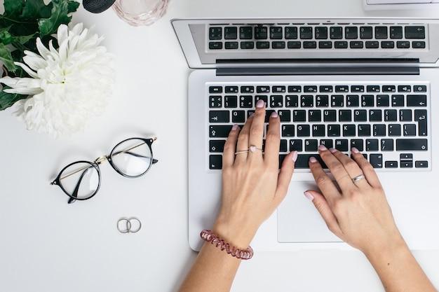 Le mani femminili usano la tastiera del computer portatile sulla tavola bianca