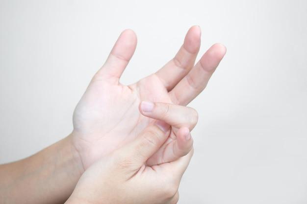 Le mani giovani hanno dolore nelle mani e massaggiano le dita dolorose. concetto di assistenza sanitaria