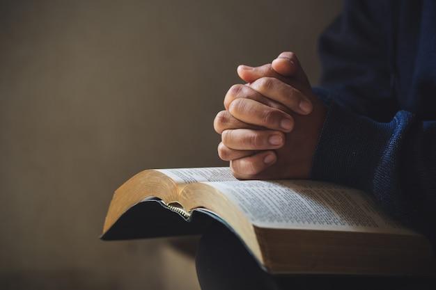 Le mani giunte in preghiera su una sacra bibbia nel concetto di chiesa per la fede