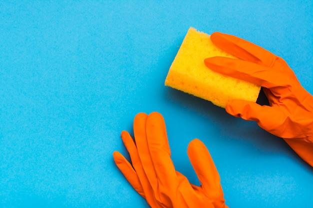 Le mani in guanti di gomma arancioni tengono nuove spugne colorate per lavare i piatti su una priorità bassa blu