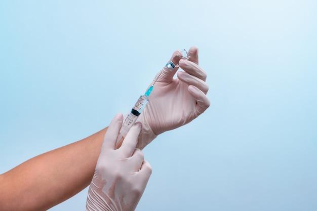 Le mani in guanti di lattice medico stanno prendendo la medicina da un'ampolla. il concetto di farmacologia.