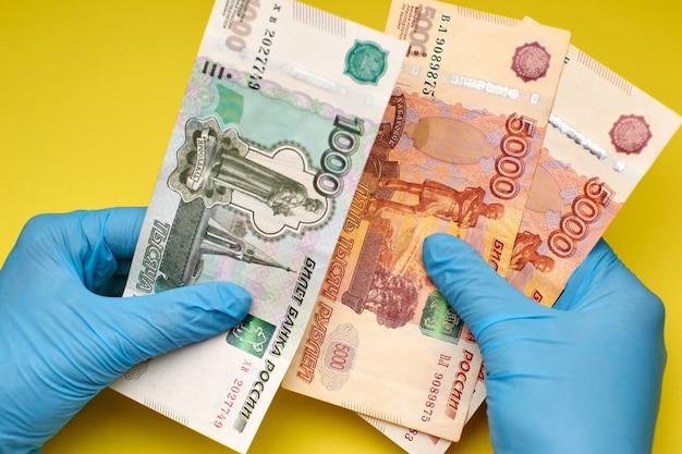 Le mani in guanti tengono i soldi su uno sfondo giallo.
