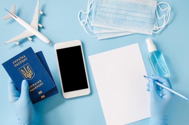 Le mani in guanti usa e getta tengono il passaporto ucraino con modello di aeroplano, maschera facciale e spray disinfettante per le mani