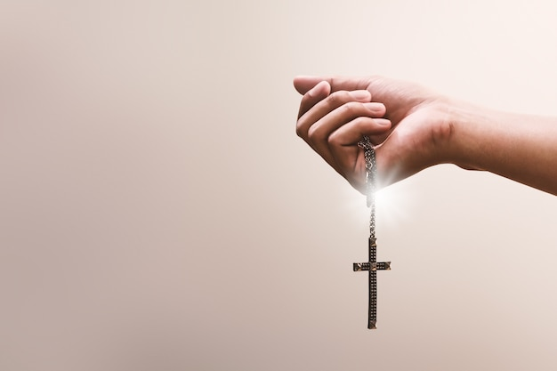 Le mani in preghiera reggono un crocifisso o una croce di collana di metallo con fede nella religione e fede in dio. potere di speranza e devozione.