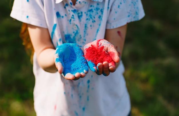 Le mani / le palme dei giovani hanno coperto i colori rossi e blu di festival di holi isolati