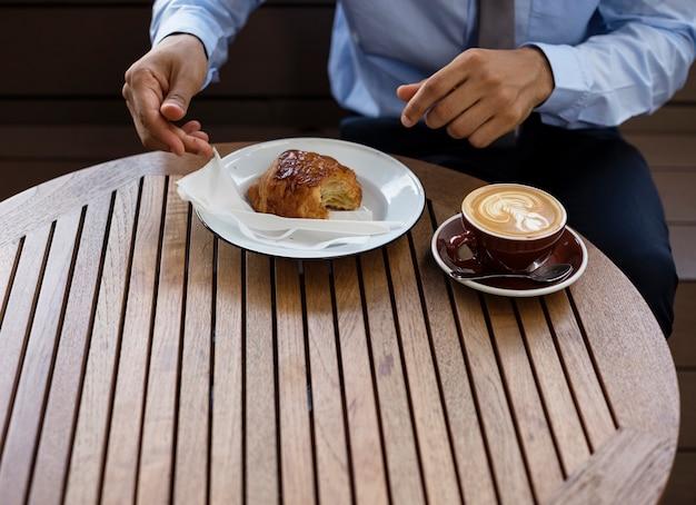Le mani mangiano il forno della rottura del caffè del croissant