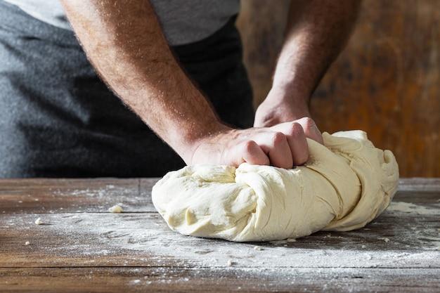 Le mani maschili impastano la pasta cucinando il pane fatto in casa