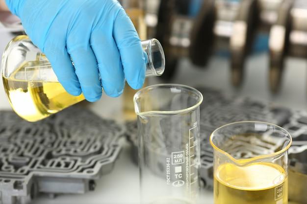 Le mani maschili nei guanti protettivi tengono in mano la provetta per test chimici del cambio automatico dell'olio motore e del booster idraulico