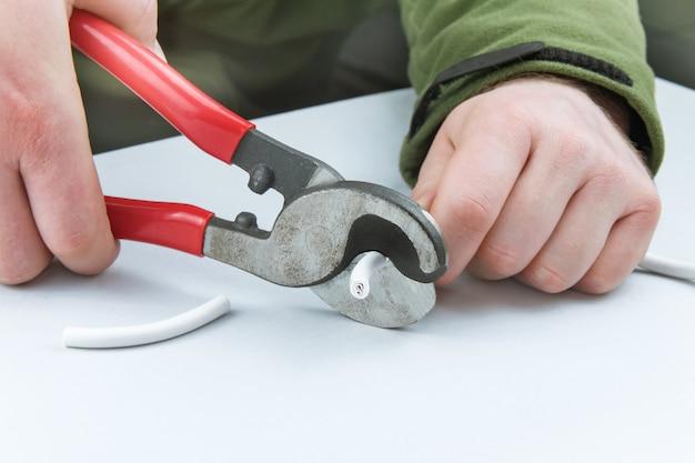 Le mani maschili tagliano un cavo bianco