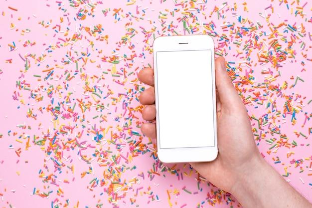 Le mani maschili tengono il telefono cellulare su una superficie rosa con dolci spruzzi multicolori