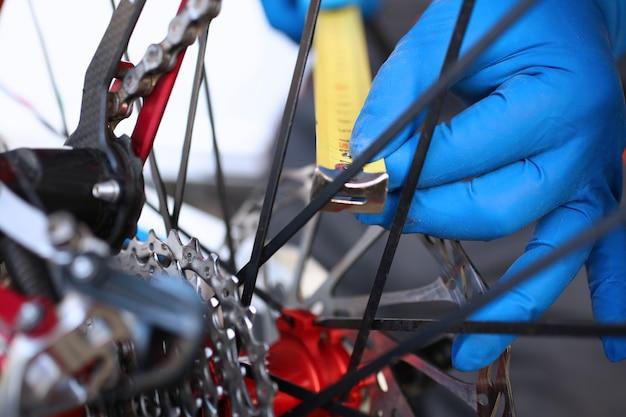 Le mani misurano con la misura di nastro nella ruota della bicicletta