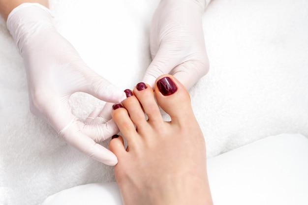 Le mani mostrano le unghie dei piedi di colore rosso.