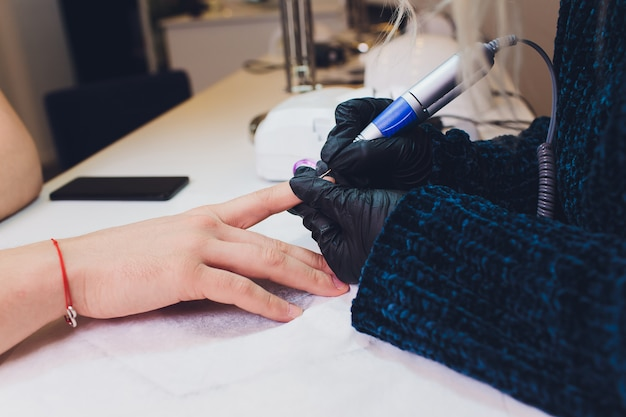 Le mani nei guanti si preoccupano delle unghie delle mani dell'uomo. manicure salone di bellezza.