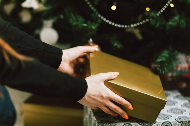 Le mani prendono il contenitore di regalo sotto l'albero di natale