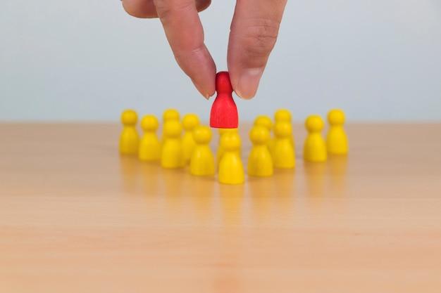 Le mani scelgono l'uomo che si distingue tra la folla.